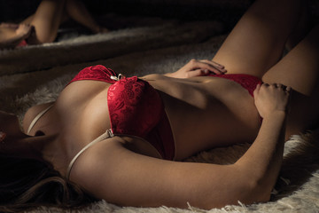 Close-up portrait of a sexy girl in red lingerie on the bed