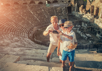 Family take vacation selfie photo on the antique theater ruins in Side, Turkey.