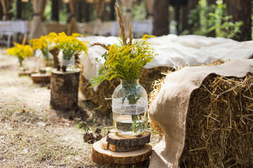 Beautifully decorated place in old autumn wood for wedding ceremony. Rustic style of elements of...
