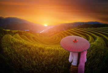 Woman holding traditional red umbrella on rice fields terraced with wooden pavilion at sunset in Mu Cang Chai, YenBai, Vietnam.