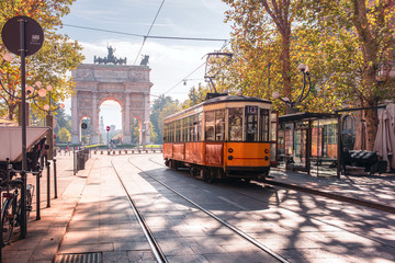 Poster de jardin Retro Famous vintage tram in the centre of the Old Town of Milan in the sunny day, Lombardia, Italy. Arch of Peace, or Arco della Pace on the background.