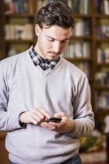 Attractive young man typing on cell phone, indoor shot in house living room