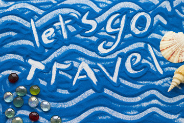 Let's Go Travel inscription on a blue colored sand with waves and travelling accessories, top view flat lay