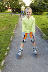 Happy family on roller skates in park. Happy family. Child and sports. Active childhood.