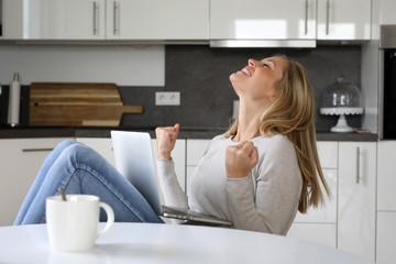 Hübsche blonde Frau sitzt mit Laptop an ihrem Küchentisch und ist begeistert