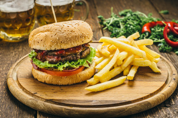 Delicious burger with beef cutlet, tomato, salad, parsley, sauce, pepper, onions, as well as French fries and beer. On a round wooden board