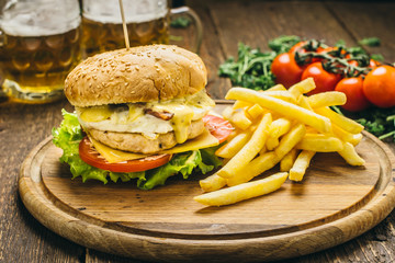 Delicious burger with chicken cutlet, cheese, scrambled eggs, tomato, sauce, salad, parsley and pepper, as well as potatoes and beer. On a round wooden board