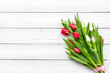 First spring flowers. Bouqet of delicate tulips on white wooden background top view copy space