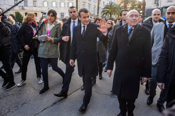 French President Emmanuel Macron, flanked by French Minister of the Interior Gerard Collomb, walks between the prefecture and the city hall of Ajaccio