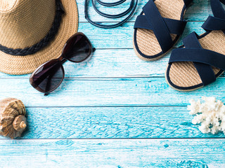 Summer background Straw hat Bracelets Sandals sunglasses Seashells on a blue table Copy space