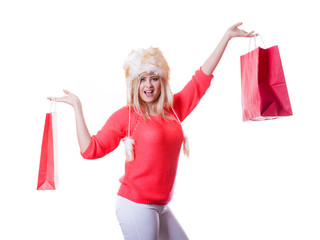 Woman wearing furry hat holding shopping bags