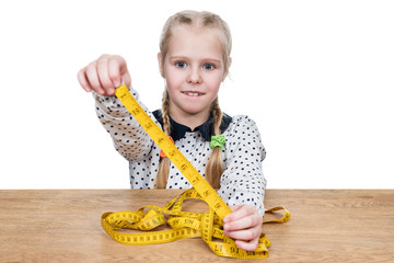 Portrait of a young girl sitting at a wooden table and looking at a yellow measuring tape, isolated on a white background