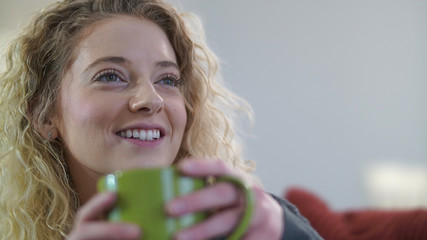 Attractive blonde woman sitting with coffee cup engaged in conversation