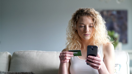 Attractive blond woman shopping online with smartphone and credit card