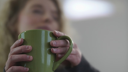 Female hands holding green coffee cup
