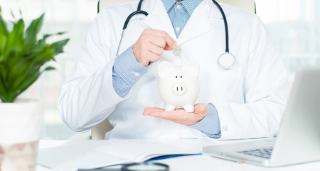 Doctor with stethoscope holding piggy bank.