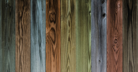 Multicolor wood boards in vertical pattern with dirty finish. Colorful wooden background with grain and knots.
