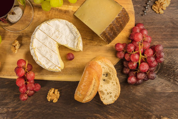 Cheese, grapes, and corkscrew on rustic texture with copyspace
