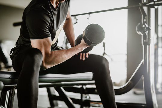 cropped shot of fitness man doing concentration curls excercise working out with dumbbell in gym. Weight training concept.