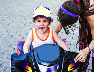 A little boy is capricious and crying, sitting on a children's ATV near the house. Children's games in the open air, walking and playing with a child on the street
