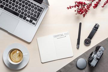 Shopping list written on open notepad in office as flatlay