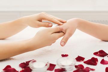 Hand massage at spa salon on white towel