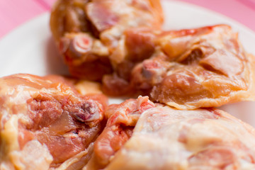 Raw chicken thighs on a white plate.