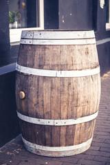 Empty beer barrel in street outside, closeup. Toned