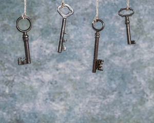 Four old rusty keys hanging on grunge abstract background with copy space. Toned