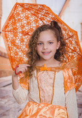 Portrait of little girl wearing a beautiful colonial costume and holding an orange umbrella in a blurred background