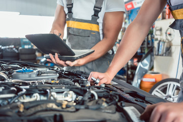 Close-up of a screwdriver held by a skilled mechanic, before repairing the engine after scanning the errors with a diagnostic software in a modern automobile repair shop