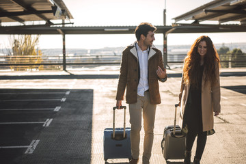 Couple with baggage on parking lot