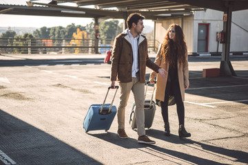 Couple walking and talking with luggage