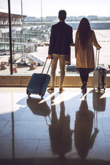 Couple with suitcases at window