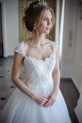 Beautiful bride in wedding dress before wedding ceremony in great hall