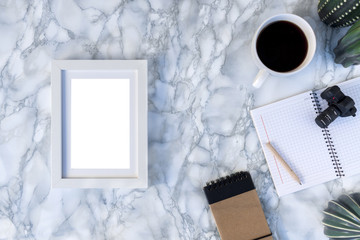 View of a marble table from above with a white empty frame, a white cup of coffee, a notebook and a ceramic cactus