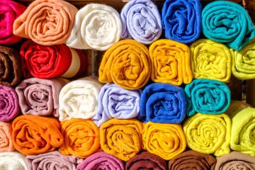 Echarpes multicolores en laine, enroulées.
