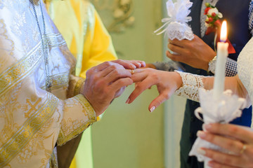 Bride and groom are holding each other's hands during church wedding ceremony