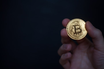 Hand holding cryptocurrency golden bitcoin isolated on dark blue background. Symbol of virtual crypto currency.