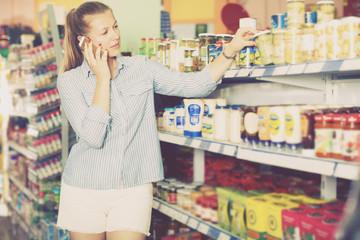 Woman is talking phone and choosing mushrooms