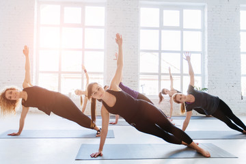 Group of six sporty women practicing yoga lesson with instructor, workout in front of windows and doing exercise on the floor in white hall of yoga studio. Teamwork, good mood and healthy life concept