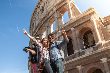 Three young friends tourists posing for funny pictures in front of colosseum in rome. Blue sky and lens flare on sunny day.
