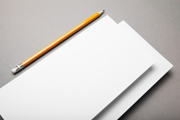 Blank paper and yellow pencil on grey background. View from above