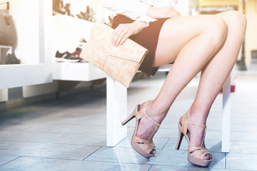 Close-up image of young woman who is posing with new handbag and fashion footwear