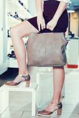 Close-up photo of female customer who is posing with handbag