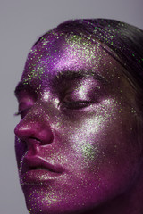 The girl in colourful blows of paint, cosmetics. The fashionable photo combining art and creativity. Space, star make-up. Gloss and shine of skin