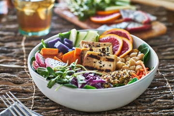 colorful buddha bowl with grilled tofu and pea shoots