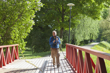 The man goes with a photo tripod on the red bridge in the park in the summer afternoon (park Toompark, Tallinn)