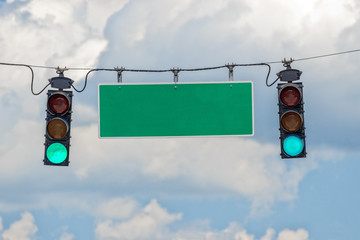 Horizontal shot of a green traffic light with a blank green sign.  Blue sky with clouds behind it.