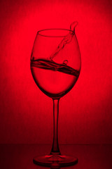 Splash of water in a wine glass on a red background